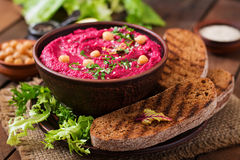 Roasted Beet Hummus with toast in a ceramic bowl Royalty Free Stock Images