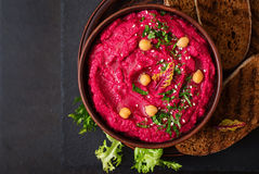 Roasted Beet Hummus with toast in a ceramic bowl on a dark background. Royalty Free Stock Photos