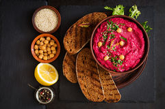 Roasted Beet Hummus with toast in a ceramic bowl on a dark background. Stock Images