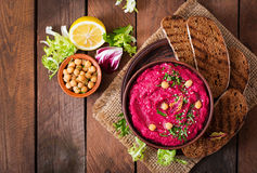 Roasted Beet Hummus with toast in a ceramic bowl on a dark background. Stock Photos
