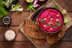 Roasted Beet Hummus with toast in a ceramic bowl on a dark background.