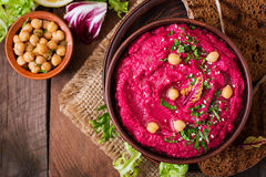 Roasted Beet Hummus with toast in a ceramic bowl on a dark background. Royalty Free Stock Images
