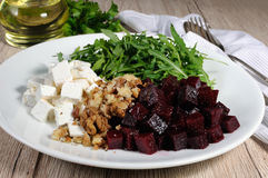 Roasted beets, arugula, cheese feta, and walnuts. Ingredients for the preparation of salad from roasted beets, arugula, cheese feta, and walnuts. Horizontal shot stock photography