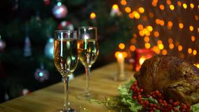Christmas table setting with turkey. A roasted bird on a platter with a salad next to a glass of champagne stands on a table amidst yellow electric lights with stock video
