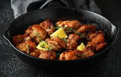 Roasted boneless skinless chicken thighs in lemon and thyme dressing served in vintage cast iron skillet, frying pan royalty free stock image