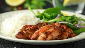 Roasted boneless skinless chicken thighs with rice and green vegetables mix stock photo