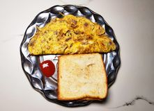 Roasted bread and omelette. In the metal plate on a light background stock photos