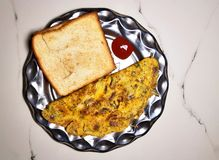 Roasted bread and omelette. In the metal plate on a light background stock image
