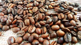 Roasted brown coffee beans on light textile cloth royalty free stock photos