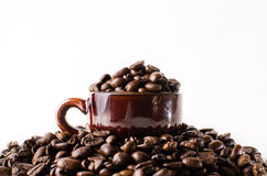 Roasted brown coffee beans. With mug Isolated  in white background Stock Photos