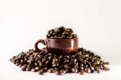 Roasted brown coffee beans. With mug Isolated  in white background Royalty Free Stock Photo