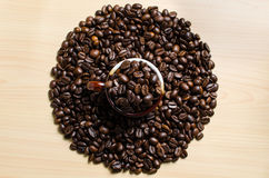 Roasted brown coffee beans. With mug on wooden table background Stock Image