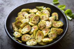 Roasted Brussel Sprouts in Black Bowl over Slate. Side view stock images