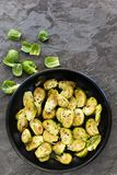 Roasted Brussel Sprouts in Black Bowl over Slate Top View. Roasted brussel sprouts in black bowl over slate. Top view royalty free stock photography