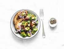Roasted brussels sprouts with bacon on a light background, top view. Delicious appetizers royalty free stock photos