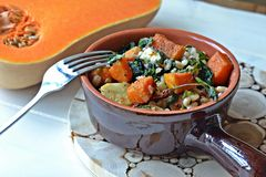Roasted butternut squash with pearl barley, spinach and creamy blue cheese Stock Image