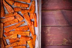 Roasted Caramelized organic Carrots with spices on black tray Stock Photos
