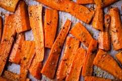 Roasted Caramelized organic Carrots with spices on black tray Stock Photo