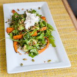 Roasted Carrots with arugula pepitas and farro. Healthy summer salad of sour cream carrots on a white plate Stock Image