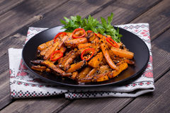 Roasted carrots in black plate, close up Royalty Free Stock Image
