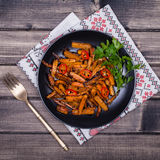 Roasted carrots in black plate, close up Royalty Free Stock Images