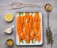 Roasted carrots with green herbs, garlic ,lemon and honey on gray concrete background, top view, flat lay. Healthy , clean food or. Vegetarian cooking and Stock Photography