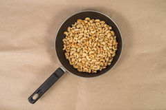 Roasted cashews in frying pan on paper Royalty Free Stock Images