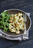 Roasted cauliflower and fresh green salad on a brown plate Stock Photography