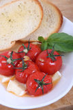 Roasted cherry tomato antipasto. With bread stock photography