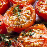 Roasted Cherry Tomatoes. With herbs, on a baking tray straight from the oven Stock Photos