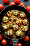 Roasted cherry tomatoes stuffed with herb pesto and mozzarella cheese on a cast-iron frying pan. Vegetarian dish, Roasted cherry tomatoes stuffed with herb pesto royalty free stock image