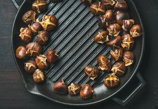 Roasted chestnuts in grilling pan over dark scorched wooden background royalty free stock photo