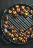 Roasted chestnuts in grilling pan over dark scorched wooden background. Roasted chestnuts in cast iron grilling pan over dark scorched wooden background, top Royalty Free Stock Image