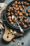 Roasted chestnuts in cast iron grilling pan over wooden board royalty free stock images