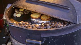 Roasted chestnuts are cooked in an iron barrel stock images