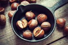 Roasted chestnuts on frying pan. Top view. Stock Image