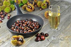 Roasted chestnuts with glass of white wine Royalty Free Stock Photography