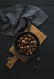 Roasted chestnuts in iron skillet pan on rustic wooden board over black table background, top view. Stock Images