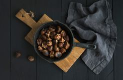Roasted chestnuts in iron skillet pan on rustic wooden board stock photography