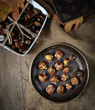 Roasted chestnuts in pan on rustic background Stock Images
