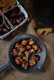 Roasted chestnuts in pan on rustic background Stock Image