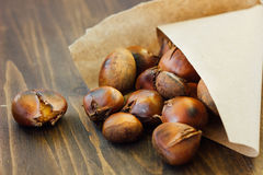 Roasted chestnuts in paper cornet. Over rustic table Stock Photography
