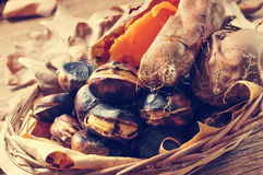 Roasted chestnuts and roasted sweet potatoes in a basket Stock Image