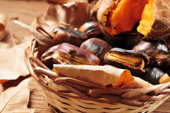 Roasted chestnuts and roasted sweet potatoes in a basket. Some roasted chestnuts and some roasted sweet potatoes in a wicker basket with autumn leaves, on a Royalty Free Stock Images