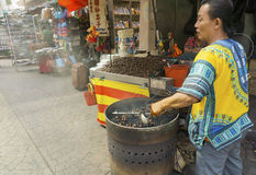 Roasted chestnuts seller. KUALA LUMPUR, MALAYSIA - January 17: Hawker roasting chestnuts in Petaling Street Chinatown on January 17, 2015 in Kuala Lumpur stock photo