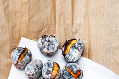 Roasted chestnuts served on white and brown craft paper with cop Stock Images