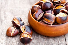 Roasted  chestnuts on wooden background Royalty Free Stock Photo