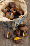 Roasted chestnuts on wooden surface Stock Photography