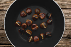 Roasted chestnuts on a wooden table Royalty Free Stock Photos