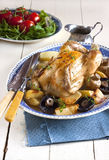 Roasted chicken. With potatoes, mushrooms and fresh thyme on blue plate ready for carving. French country style with rustic wooden table, old blue napkin and royalty free stock photos